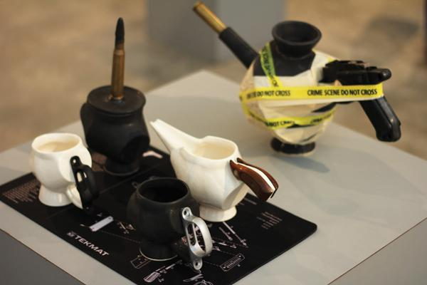 "student Amy Titus' third-place ceramic and mixed media piece, ""Gun Debate Over Coffee,"" lies among the Juried Student Art Exhibition held May 8."
