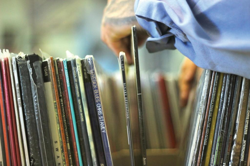 Photo by Wanz Dover | A customer shuffles through stacks of vinyl records.