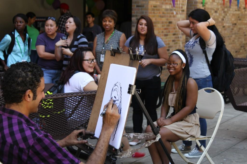 Photo by Willie R. Cole | Caricature artist Sami Aly draws his parody illustration of Brookhaven College student Desiree Island as students line up to have their portraits sketched at the Welcome Back Carnival Sept. 10 in the Commons Courtyard.