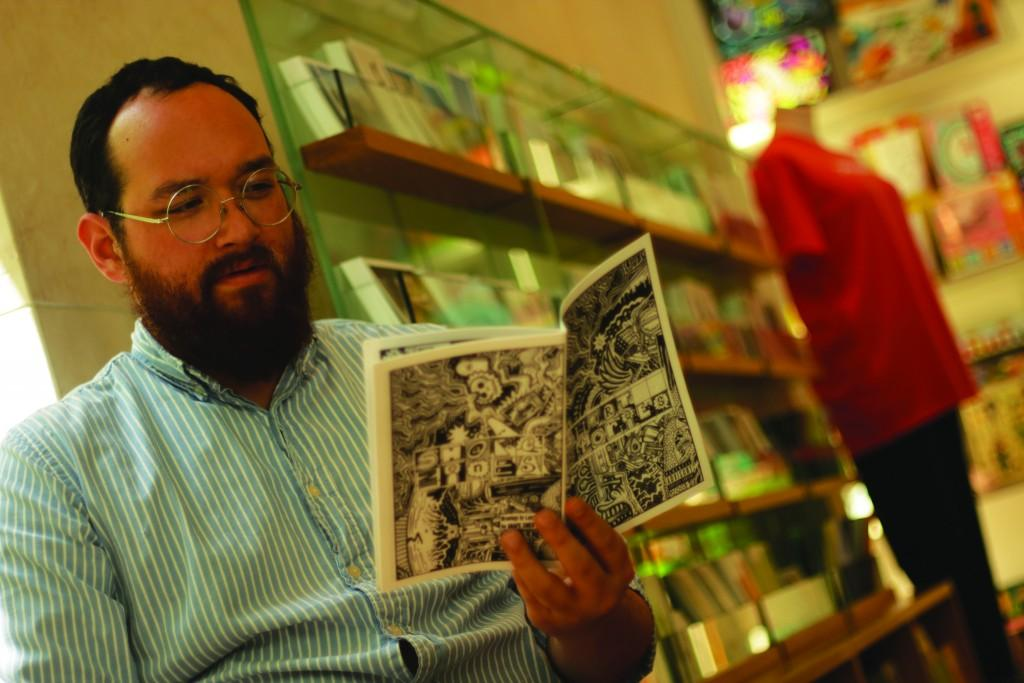 "Photo by Evan Henry | Courier Randy Guthmiller reads his latest ""SHAPES"" -published zine, Larry Cary's ""Short Stories,"" at the Nasher Gift Shop, where he works to fund his dreams."