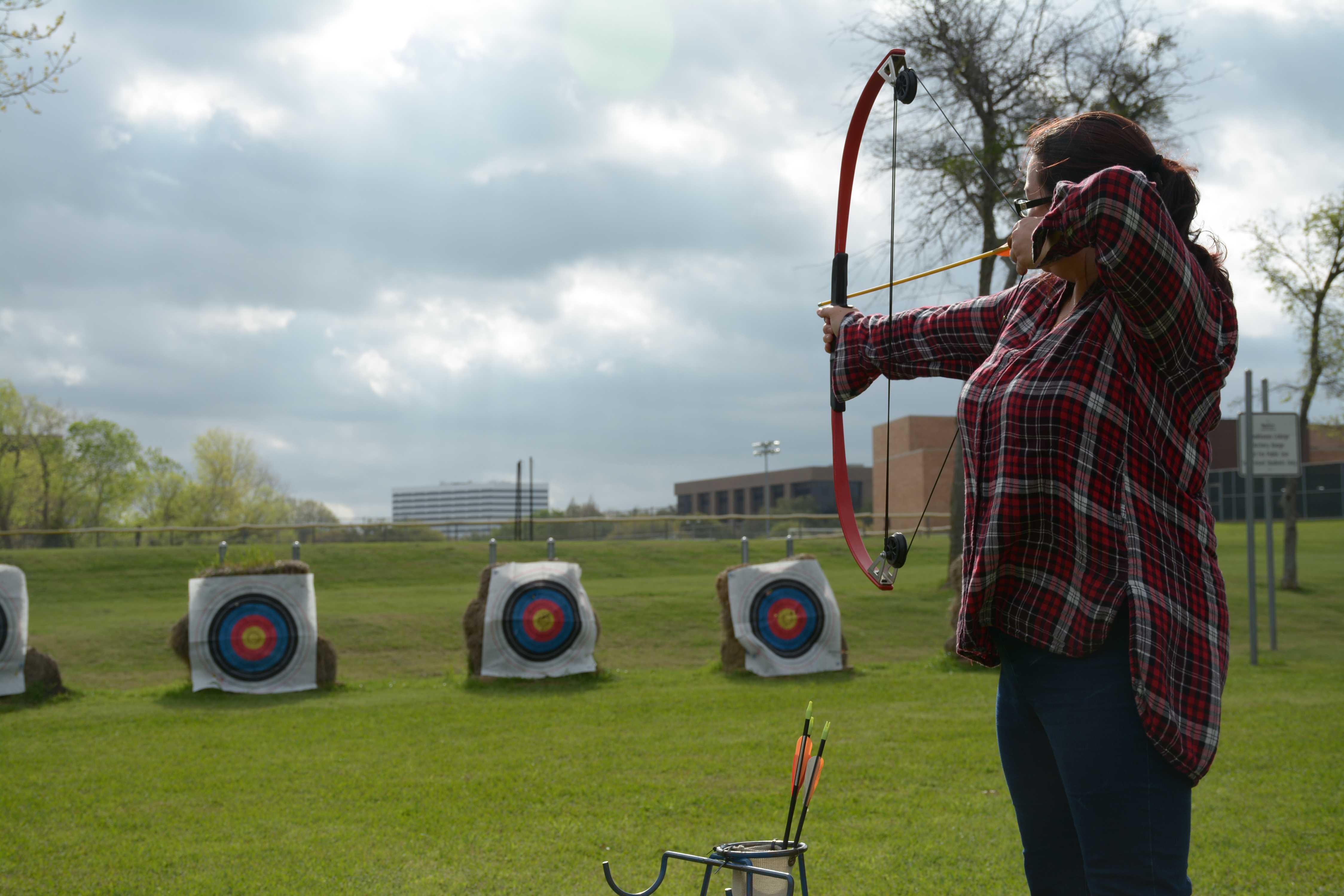 Amy Rogers, a student, prepares to shoot an arrow from her compound bow.