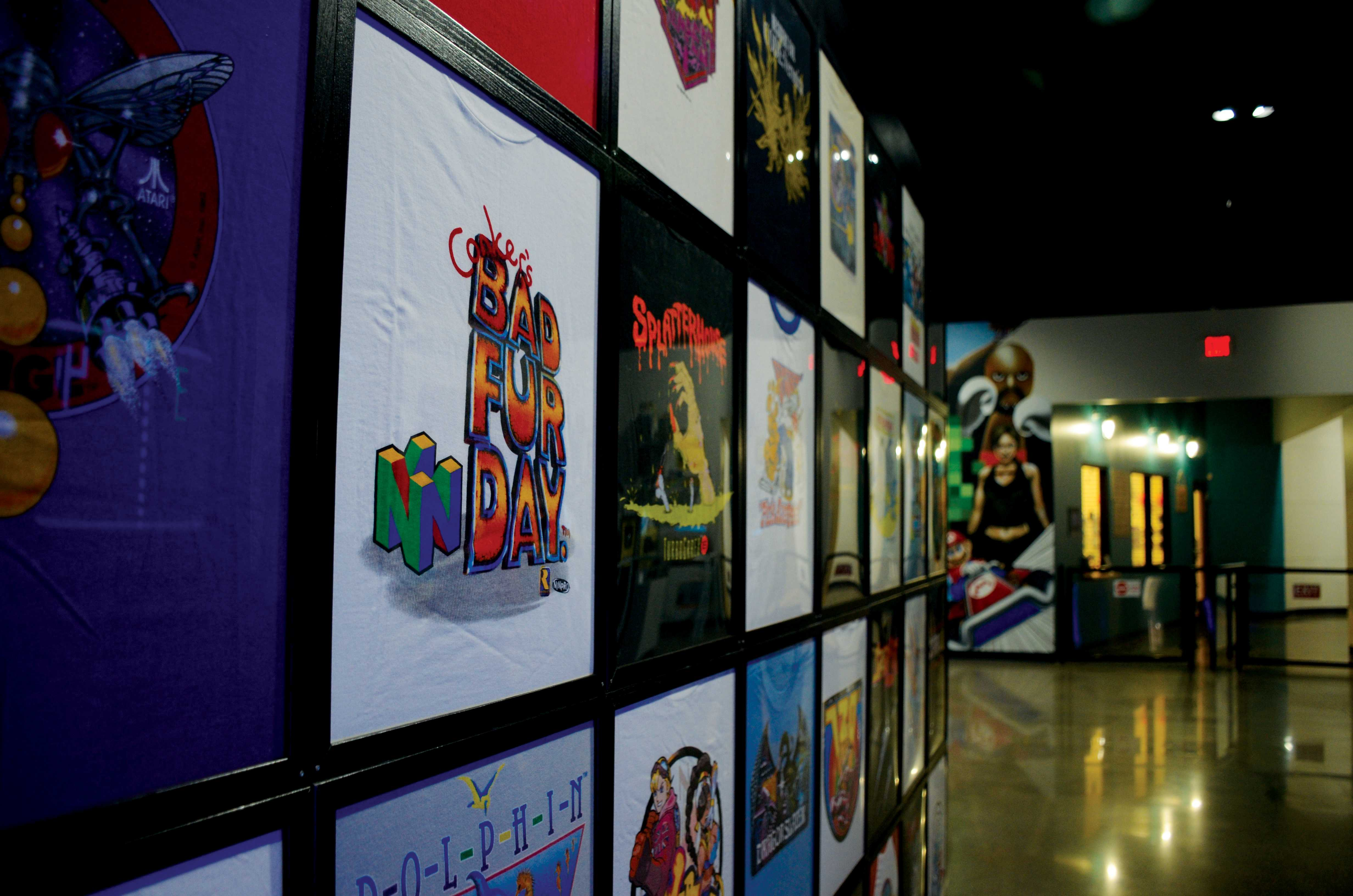 A grid of vintage video game T-shirts hang on a wall in the museum.