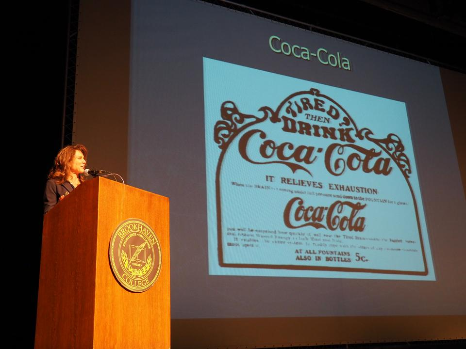 Photo by Jubenal Aguilar Monica Rankin, director of the University of Texas at Dallas Center for Latin American Initiatives, talks about the origins of Coca-Cola. The beverage, originally made from coca leaves and African kola nuts, was marketed as alleviating many of the symptoms patented medicines already were, including exhaustion.