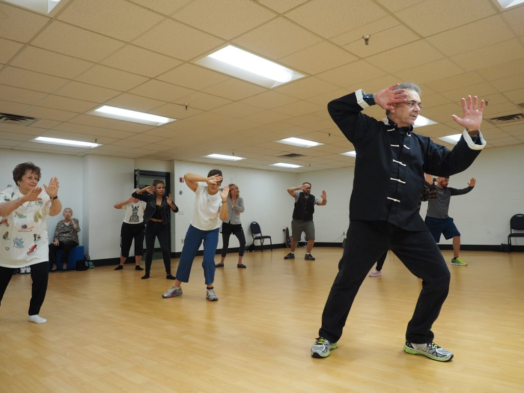 "Photo by Jubenal Aguilar Glenn Kasparian, biology professor, teaches students the ""fair lady throws shuttle"" move from the 24 form of tai chi as part of his class, Sept. 29."