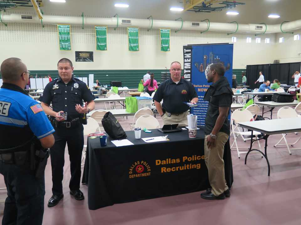 Photo by Stephon Smith Senior Cpl. Dan White (right) and Mike Friend (left) discuss the recruiting process for the Dallas Police Department for applicants during the Career Fair Oct. 13.