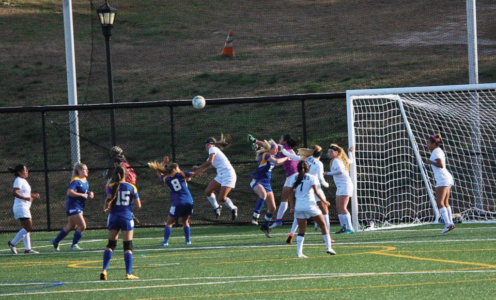 Photo courtesy of Nora Lopez Daniela Marin, Lady Bear goalkeeper, attempts to punch the ball away while teammate Brenda Hernandez (center) jumps to clear the ball from a Raptors corner kick attempt.