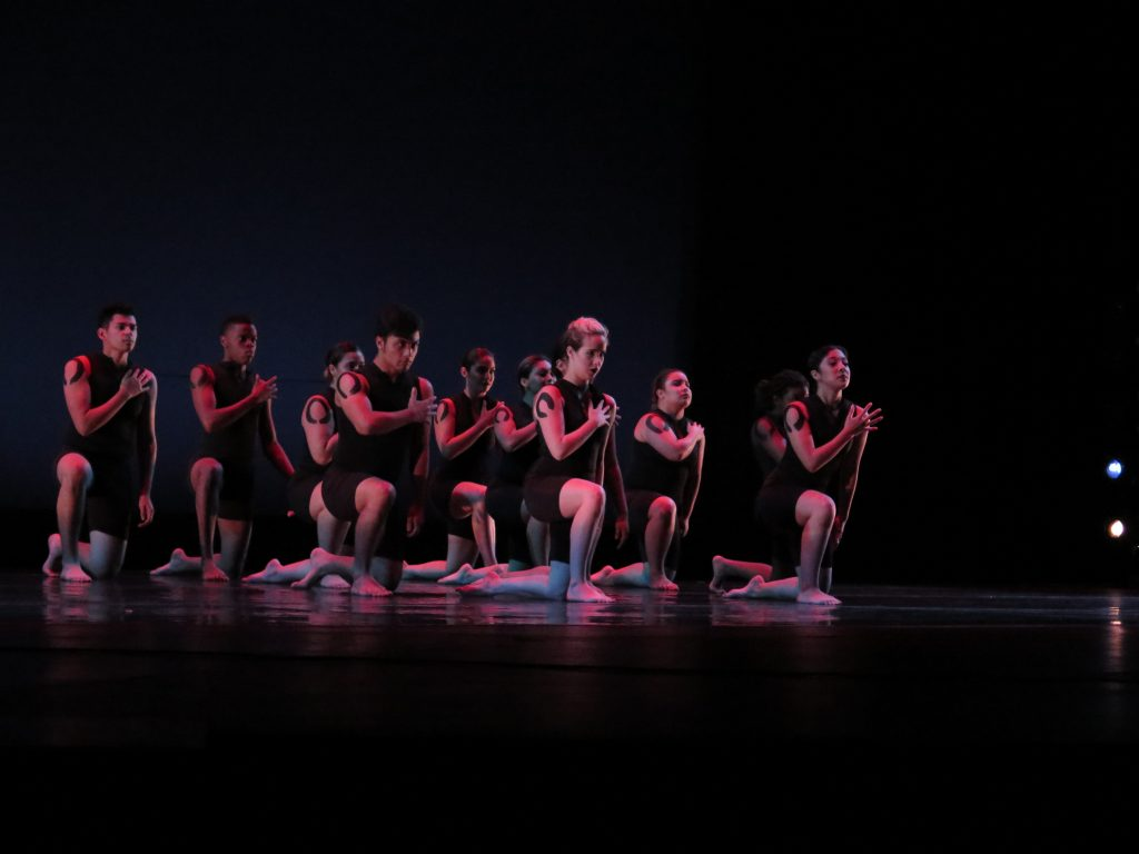 "Dance students kneel during a performance to ""Strength in serenity."""