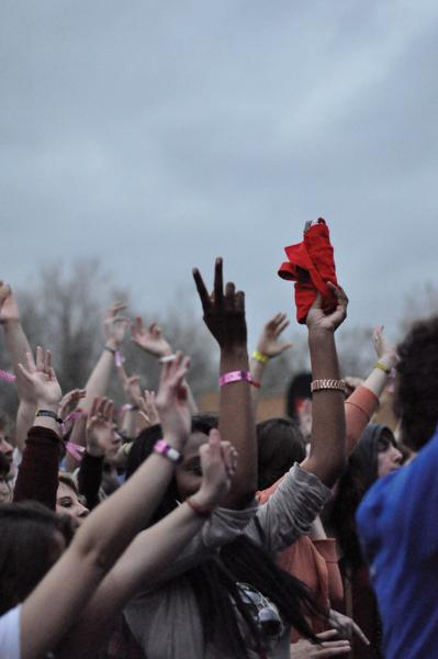 Photo by Adriana Salazar | A crowd of people at 35 Denton wave their hands in the air during a concert despite dreary weather conditions.