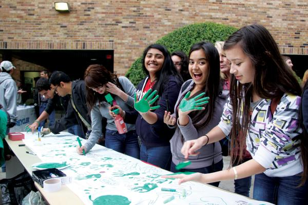A group of students make the pact to go green by placing their hand-print and signing their name in a banner.