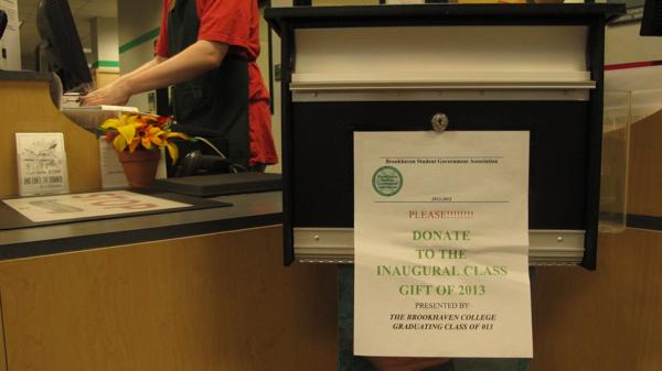Photo by Nicholas Bostick | The donation box for the SGA student gift sits in front of the cashiers inside the Brookhaven bookstore.