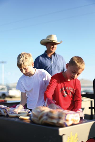Matt Kuta, his son Blaine Kuta, and his son's friend Seth Wilson, from a church in Anderson, Texas, cook up hamburgers.