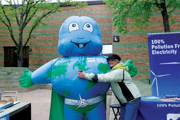 Brookhaven librarian Lois Wagenseil poses with an inflatable earth super hero.