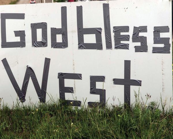 """Photos by Kathy Tran and Earl Ward    A handmade """"God bless West"""" sign serves to raise the spirits of those in the area."""