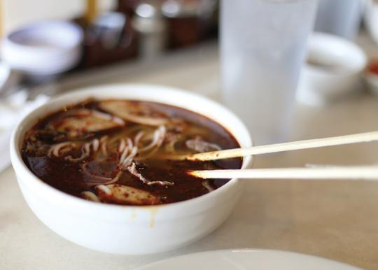 Photos by Scott Mitchell | A bowl of fiery hot bun bo hue steams after being freshly served from the kitchen.