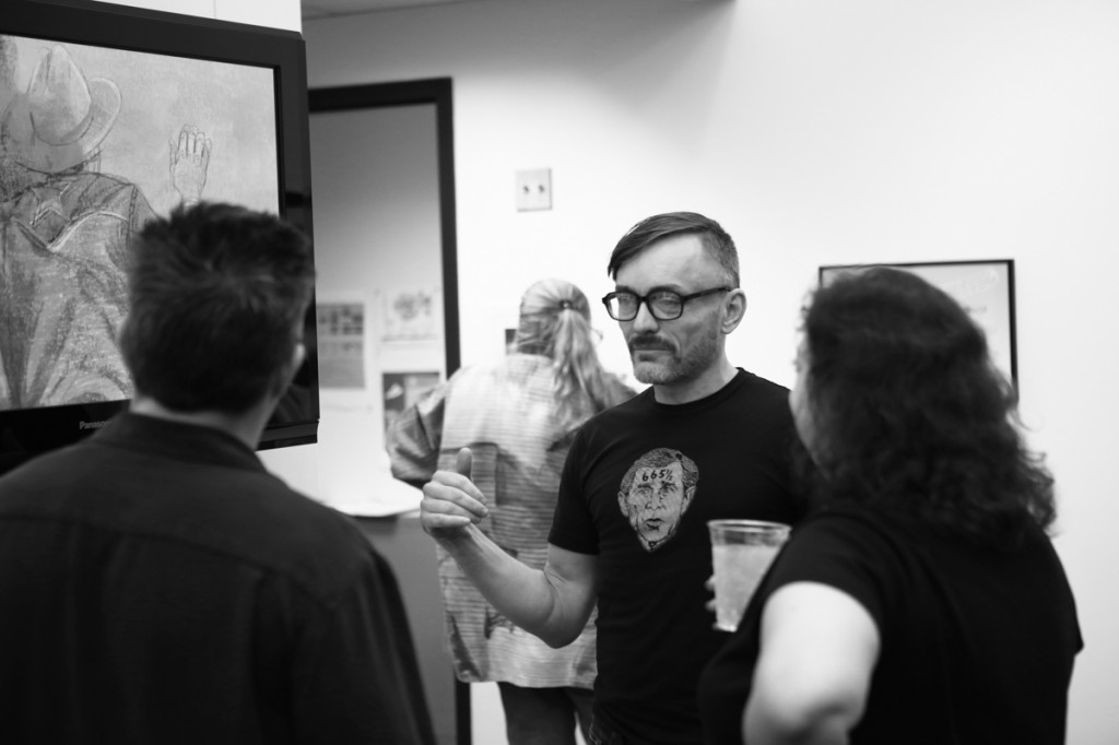 Brian Jones, an artist whose work is on display in the show, mingles with attendees