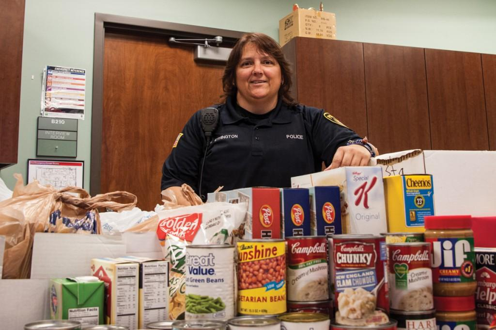 Photo by Scott Godbey | Officer Vikki Ethington stands behind the mountain of donated food items for the campus food pantry.