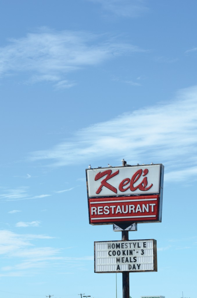 Photo by Travis Baugh  | The sign for Kel's Restaurant, worn and decorated with pigeons.