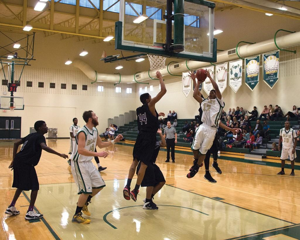 Laquin Turner (#30) drives into a congested lane and adjusts his layup acrobatically to avoid the reach of Richland College's defense