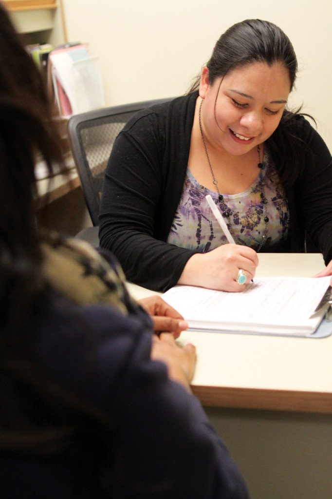 Linda Reyna helps a student fill out counseling paperwork in her office.