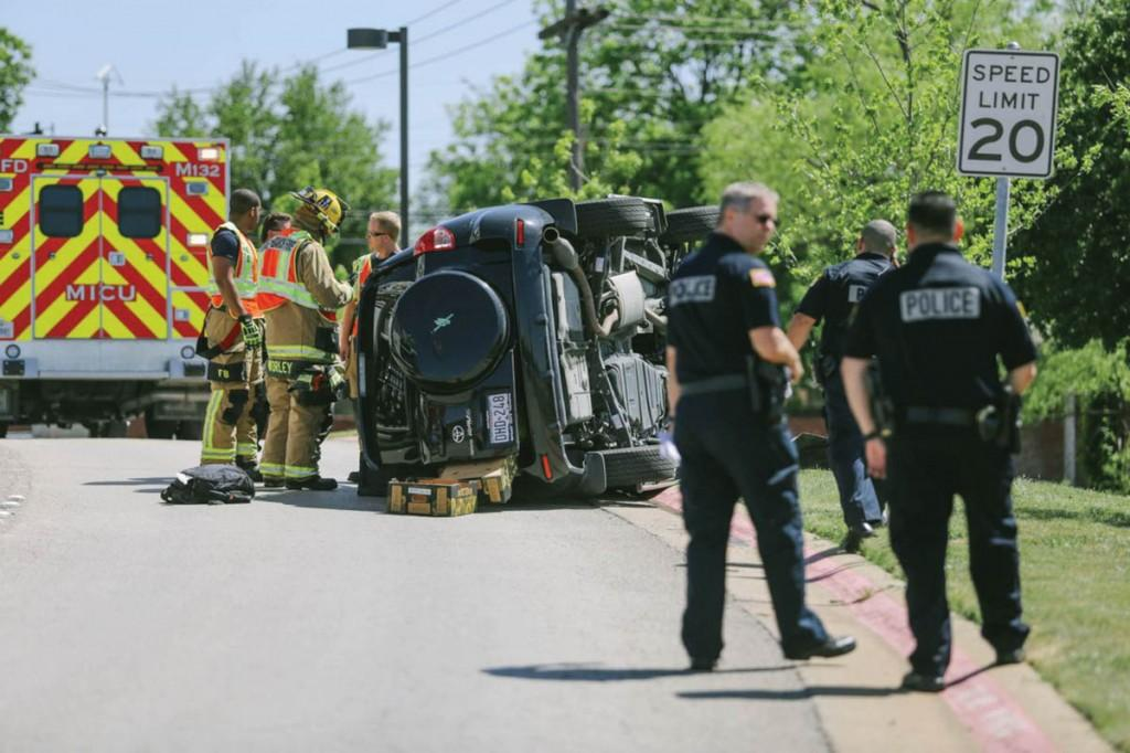 Photo by Kathy Tran | A flipped SUV rests at the Valley View Lane exit to Brookhaven College. The April 28 accident involved the use of a cell phone, according to the police report. The city of Farmers Branch passed an ordinance March 18 making text-based communications illegal while driving.