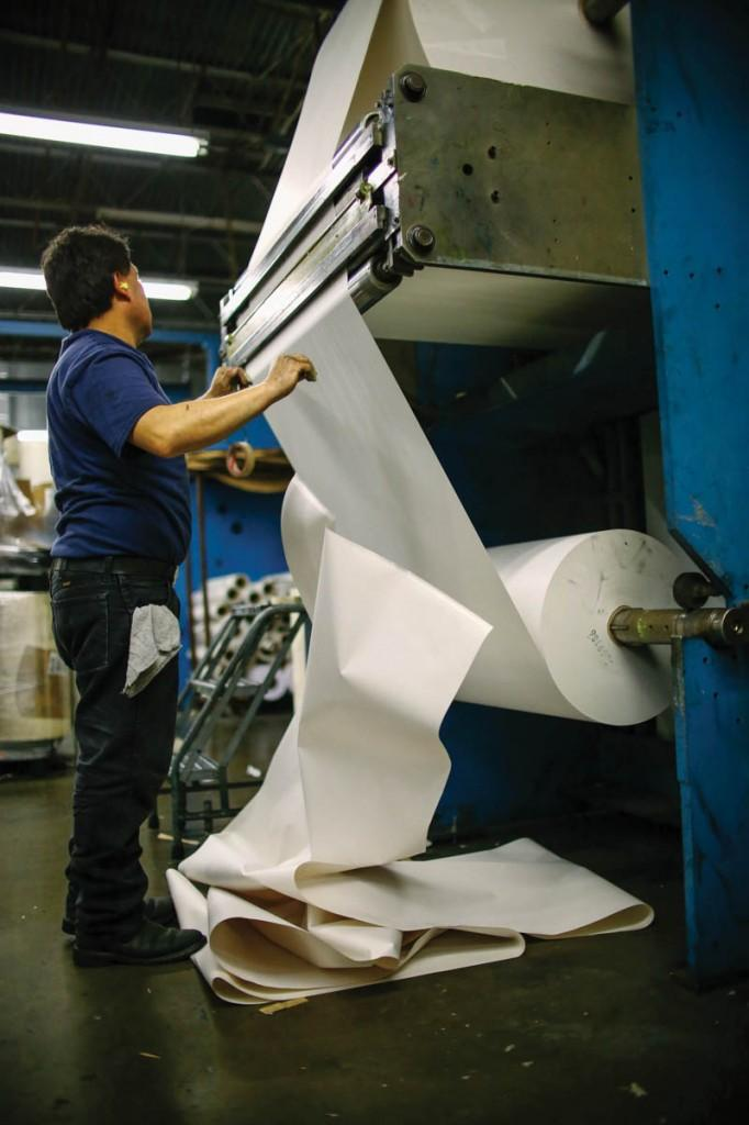 A pressman feeds a new roll on to be spliced when the other roll runs out.