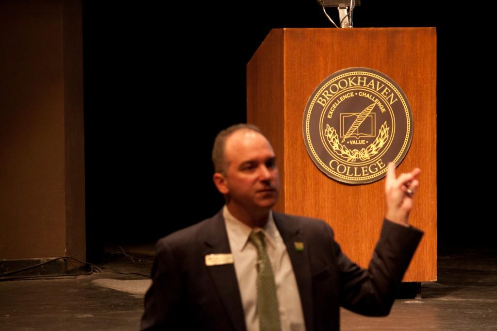 Photo by Nicholas Bostick | Brookhaven College President Dr. Thom Chesney points to the Brookhaven logo during the Sept. 2 convocation speech in the Performance Hall, where he talked about the advantages of attending community college.