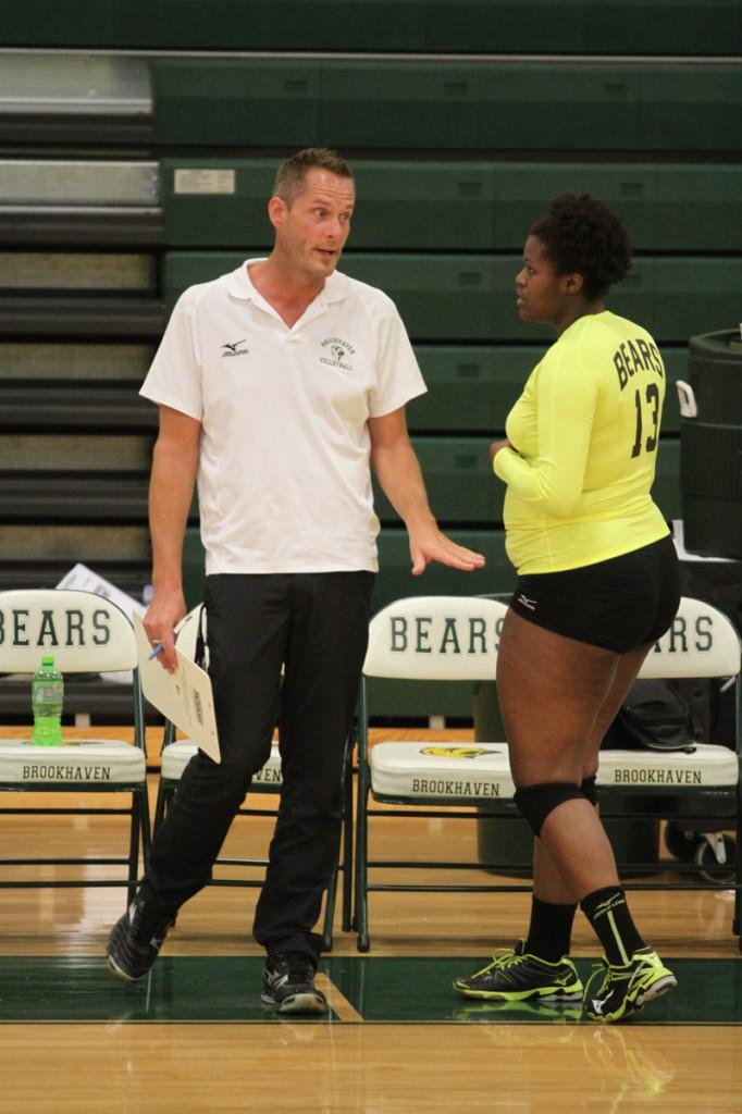 Volleyball coach Jason Hopkins gives advice to Kim Parker.