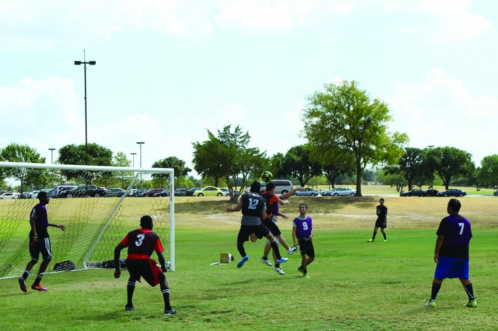 Photo by Willie R. Cole | Two intramural soccer players jump for a header as teammates look on.