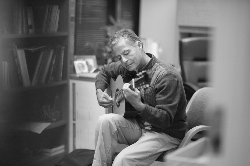 Photo by Adriana Salazar | Rodger Bennett takes a moment to strum a few bars on his guitar in his office.
