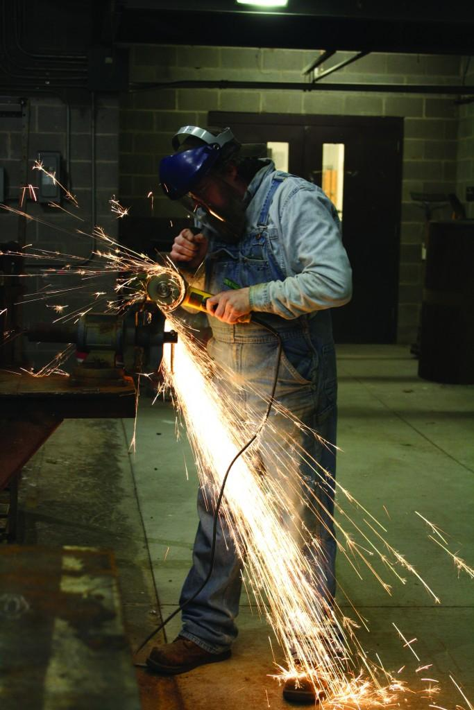 Instructor Kelly Kring prepares the metal for students' projects.