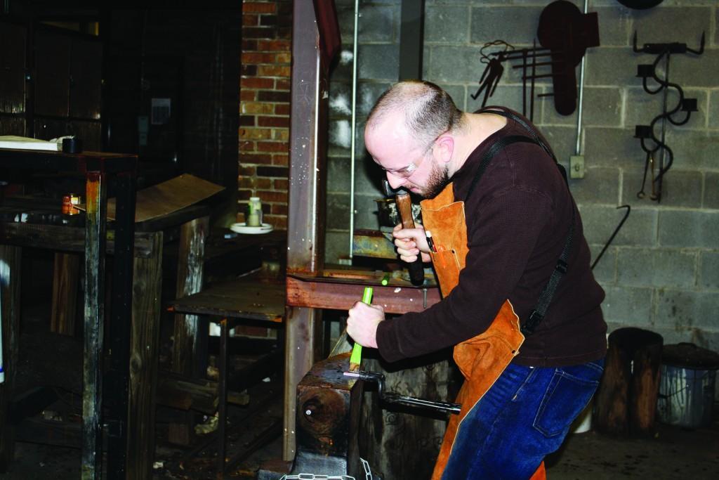 Photos by William De La Cruz   Adam Elliott uses a hammer and anvil to shape his flint striker.