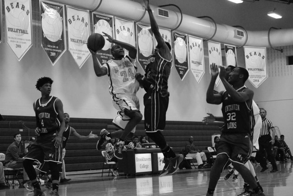 Brookhaven guard Kenny Slocum (#24) leaps for a shot at the net while surrounded by Mountain View College opposition.