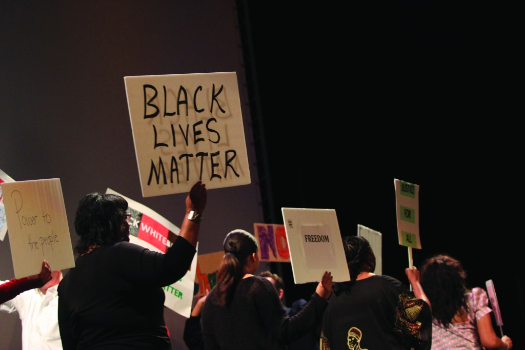 Photo by Claudia Valerio | Participants in the African American Read-In reading walk across the stage with empowering signs before passing them to attendees.