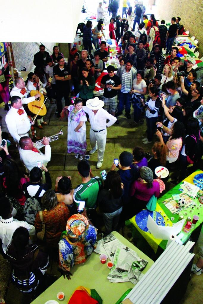 A crowd gathers to watch dancers perform a Mexican folk dance.