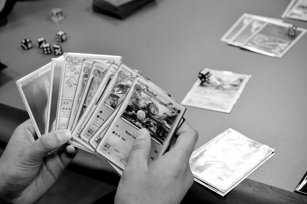 A player holds a hand of Pokémon cards