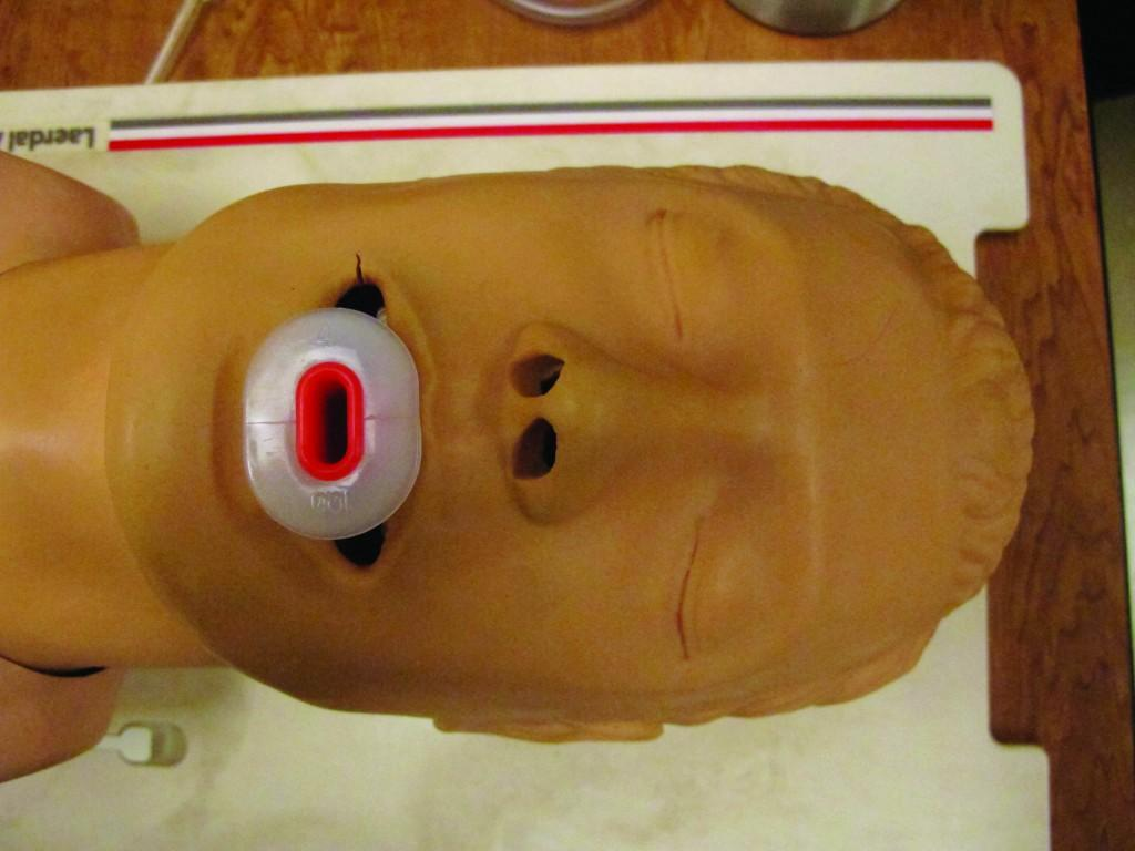 A training dummy is used to display the proper method of clearing a patient's airway.