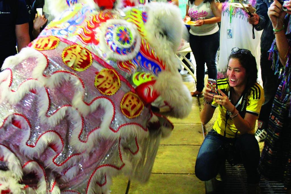 Brigitte Zumaya | Courier Brookhaven College student Vanessa Jaramillo uses her phone to capture the Chinese lion dance.