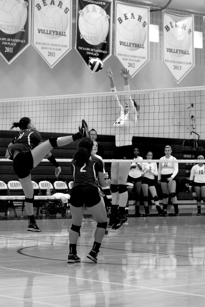 Outside hitters Megan Crown (#13) and Kelsey Rogers (#6) attempt to block a spike from an opposing Panola Fillies player
