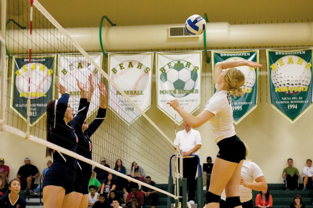 Samantha Eaton (#12) going up for a spike as two Eastfield opponents attempt a double block.
