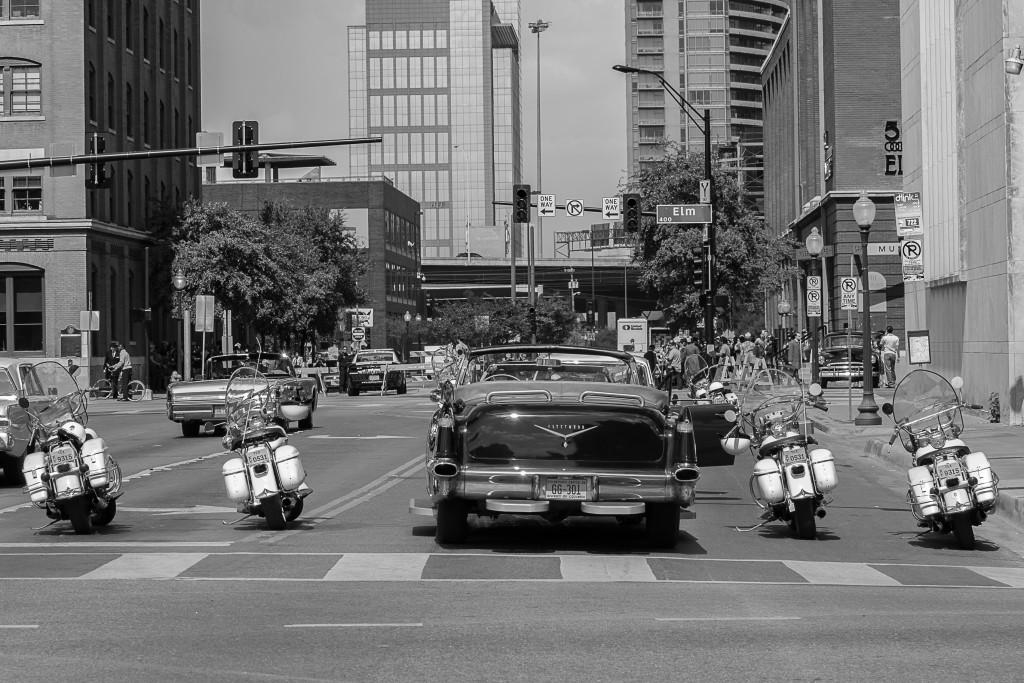 "The Kennedy era presidential limo, ""The Queen Mary,"" a 1956 Cadillac Fleetwood 75 sits flanked by police motorcycles for the upcoming motorcade scene."