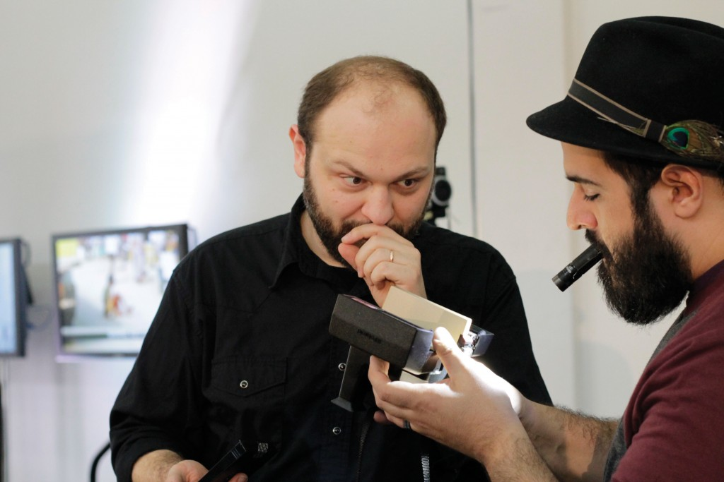 Rodrigue and Armand Kohandani, owner of the Denton Camera Exchange, examine an instant film camera.