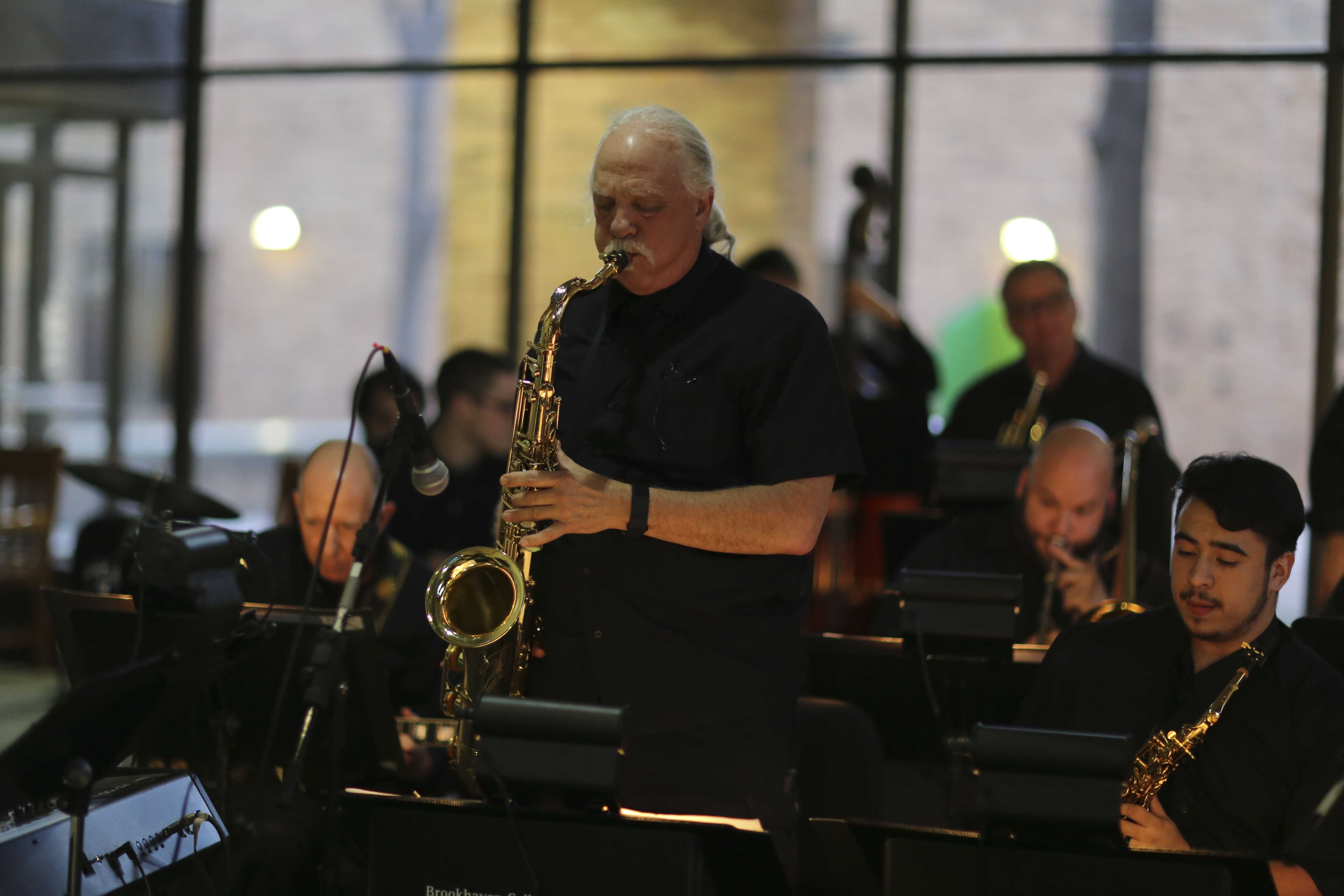 Brookhaven Big Band member Dan Ebie rocks out on his saxophone as guests mill about the Performance Hall lobby.