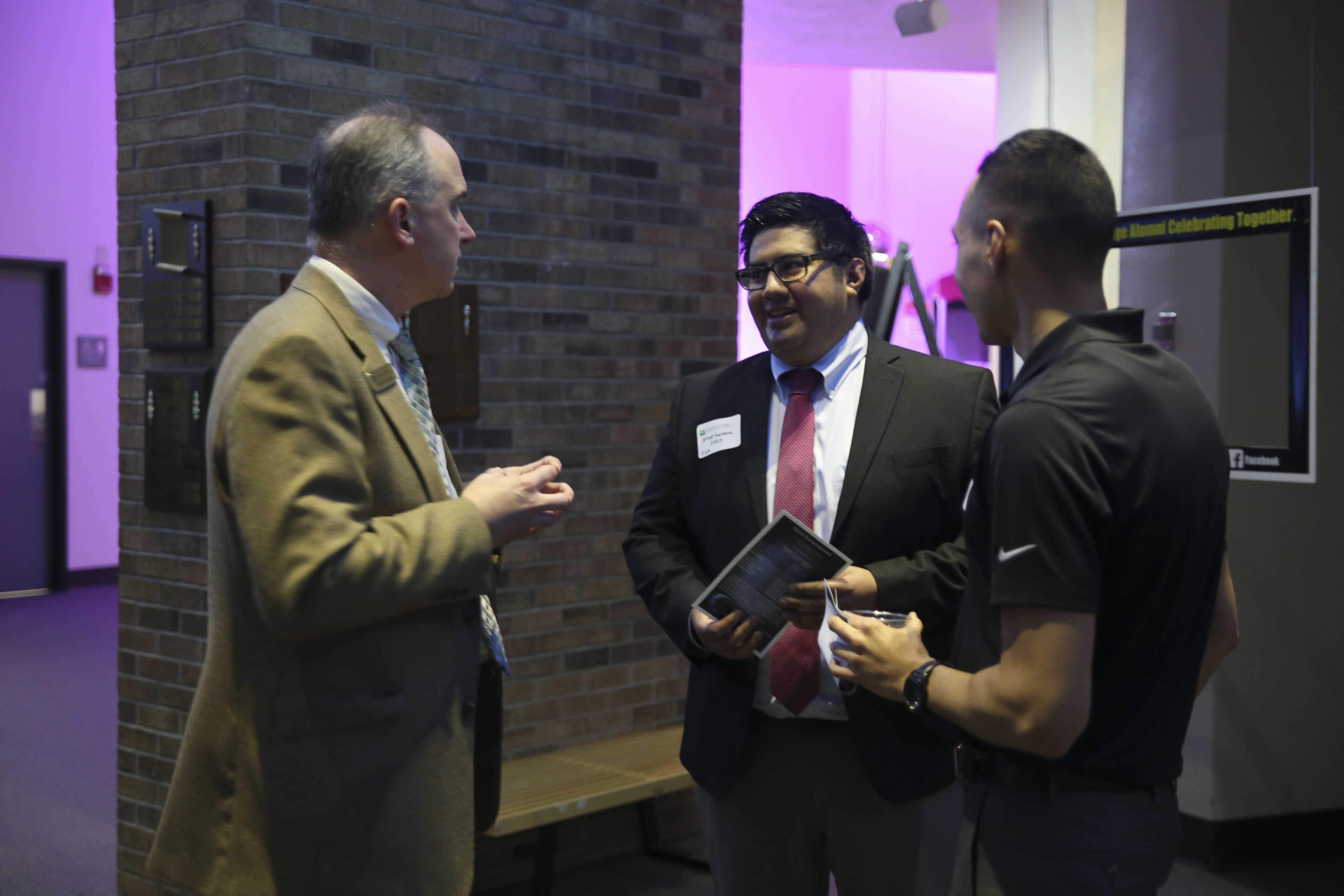 Brookhaven President Thom Chesney speaks to Brookhaven alumnus Jesse Saldana.