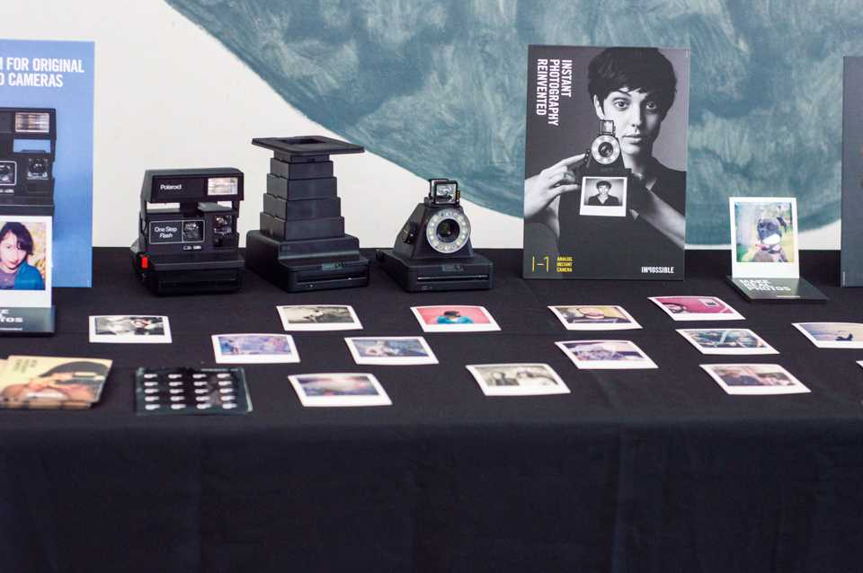 Books, instant film photographs, a Polaroid One Step camera, an Impossible Instant Lab camera and an Impossible I-1 camera line a table at PolaCon.