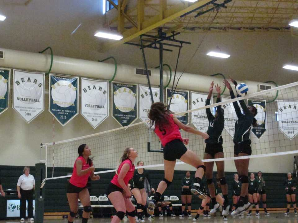 Lady Bear Kaycie Hamilton (#8) tosses the ball across the net and narrowly slips by the Fillies' defense.