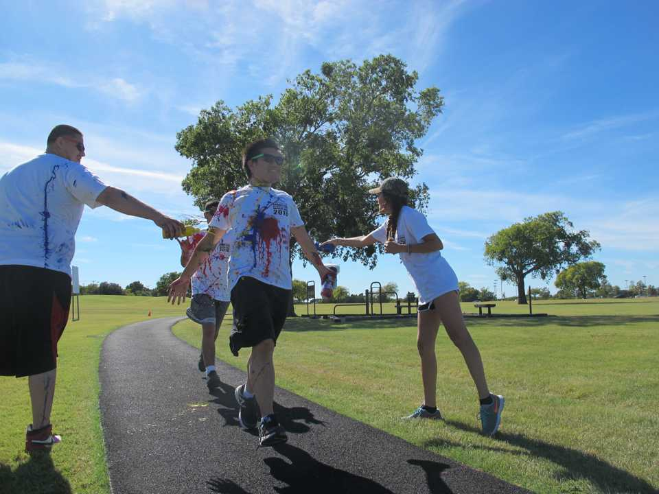 Sonia Agulera and Fernando Sanchez, Student Government Association members, throw paint on runners.