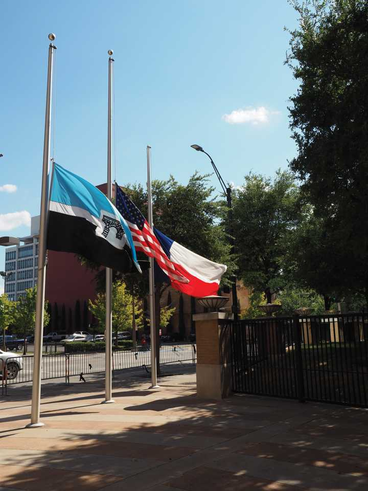 Photo by Jubenal Aguilar The El Centro, U.S. and Texas flags fly at half staff outside the front entrance of El Centro College July 19.
