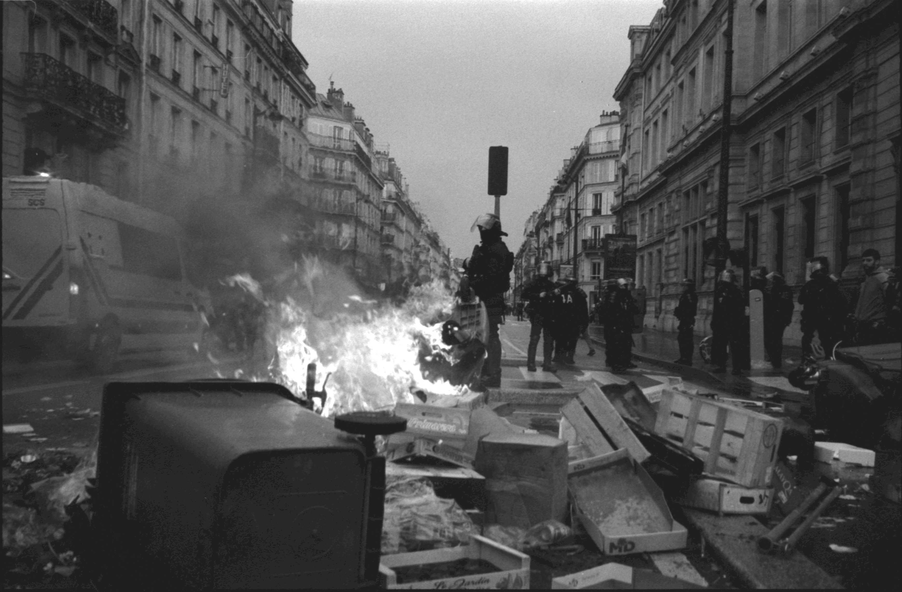 Film photo courtesy of Lev Bourliot | French police stand by burning trash in a market street after chasing away protesters.