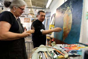 <strong>Photos by Jubenal Aguilar |</strong> Chong Chu, art professor (right), talks with Nancy Neergaard, a student, about her painting project and what she can do to improve the art piece to render a more realistic interpretation of a potato Nov. 6.