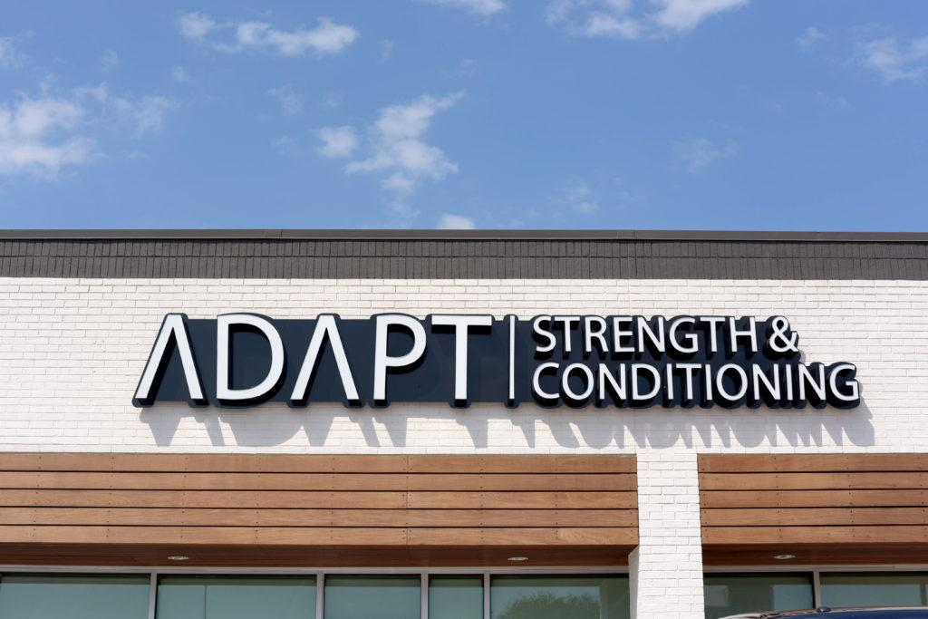 ADAPT Strength & Conditioning, printed in a white, modern font above wooden awnings on turquoise windows.